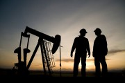 an oil well and two oil workers at dusk