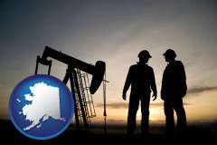 alaska map icon and an oil well and two oil workers at dusk