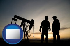 colorado an oil well and two oil workers at dusk