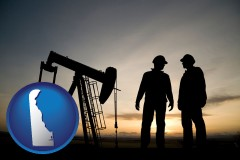delaware an oil well and two oil workers at dusk
