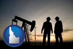 idaho an oil well and two oil workers at dusk