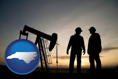 north-carolina map icon and an oil well and two oil workers at dusk