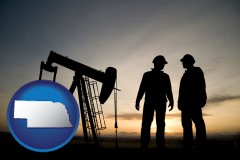 nebraska an oil well and two oil workers at dusk