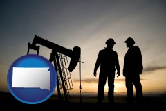 south-dakota map icon and an oil well and two oil workers at dusk