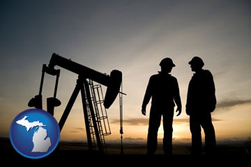 an oil well and two oil workers at dusk - with Michigan icon