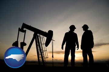 an oil well and two oil workers at dusk - with North Carolina icon