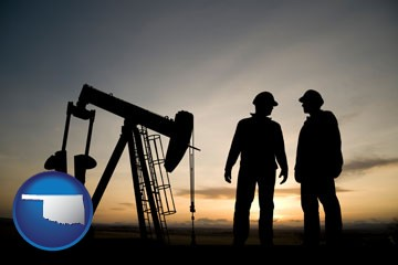 an oil well and two oil workers at dusk - with Oklahoma icon