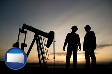 an oil well and two oil workers at dusk - with South Dakota icon